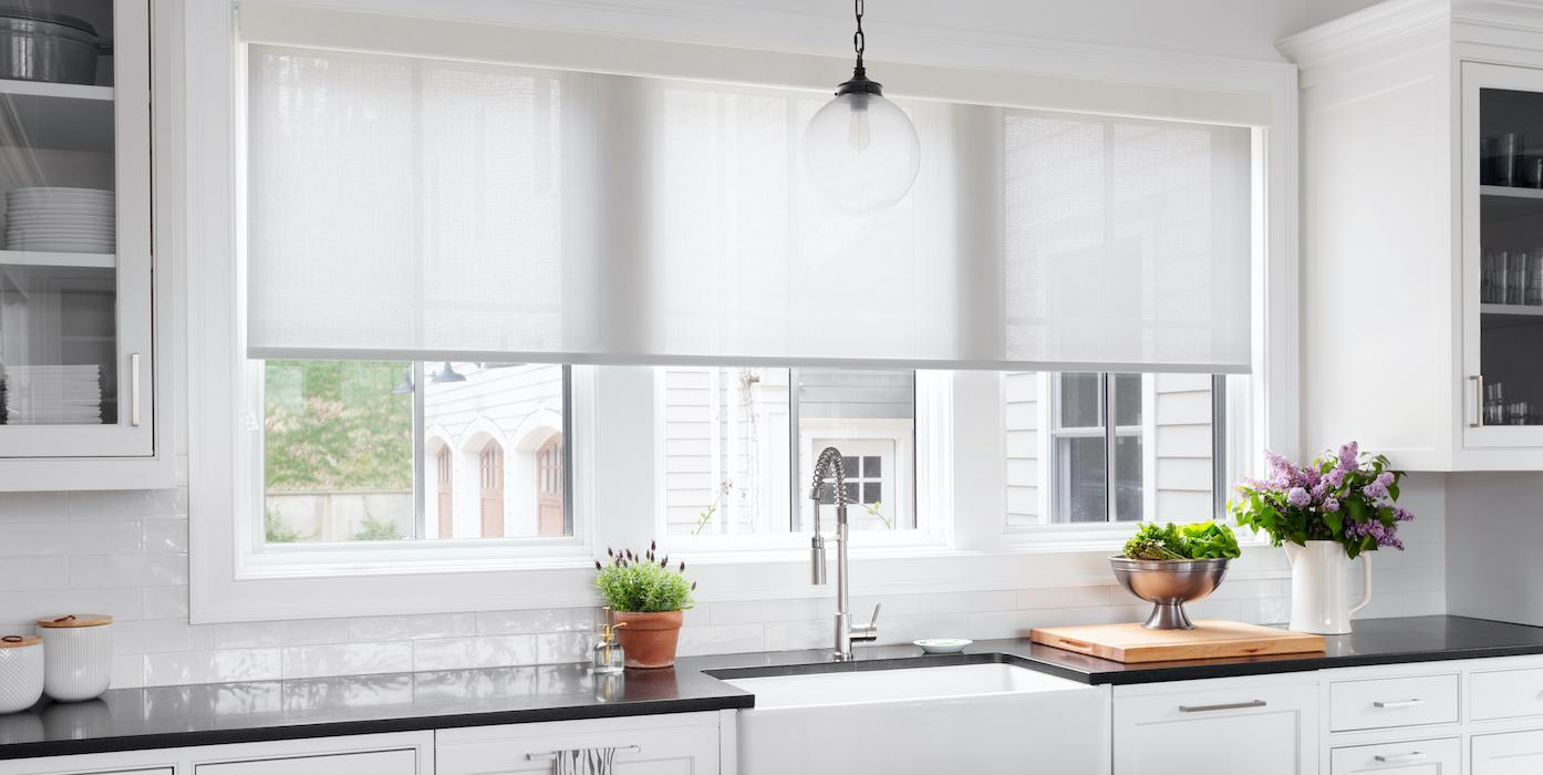 White roller shades cover a large window over a kitchen sink.