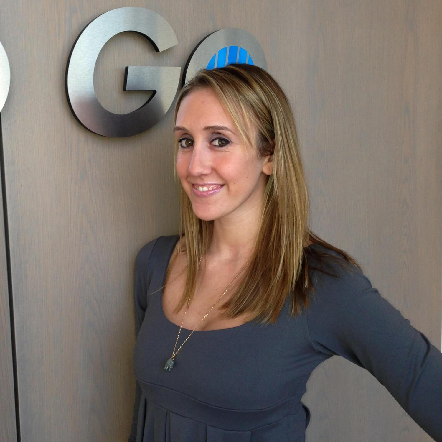 A woman smiles in front of a large Blinds To Go sign at the BTG headquarters