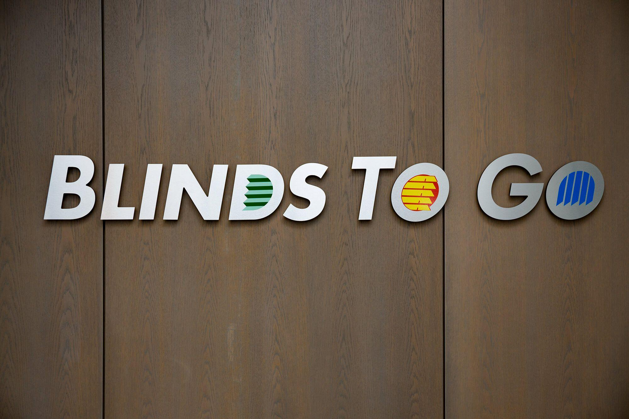Blinds To Go logo on wood background.