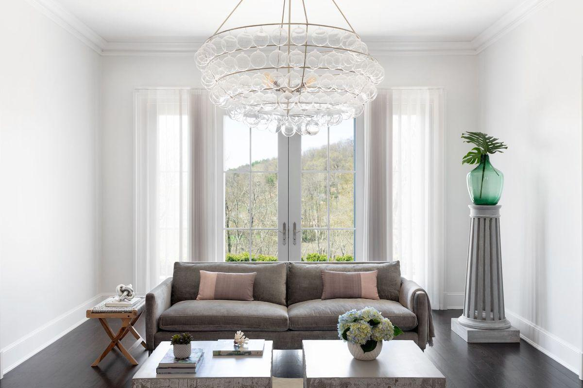 An elegant living room features a modern chandelier and tall windows and french doors partially covered by Melody sheer shades