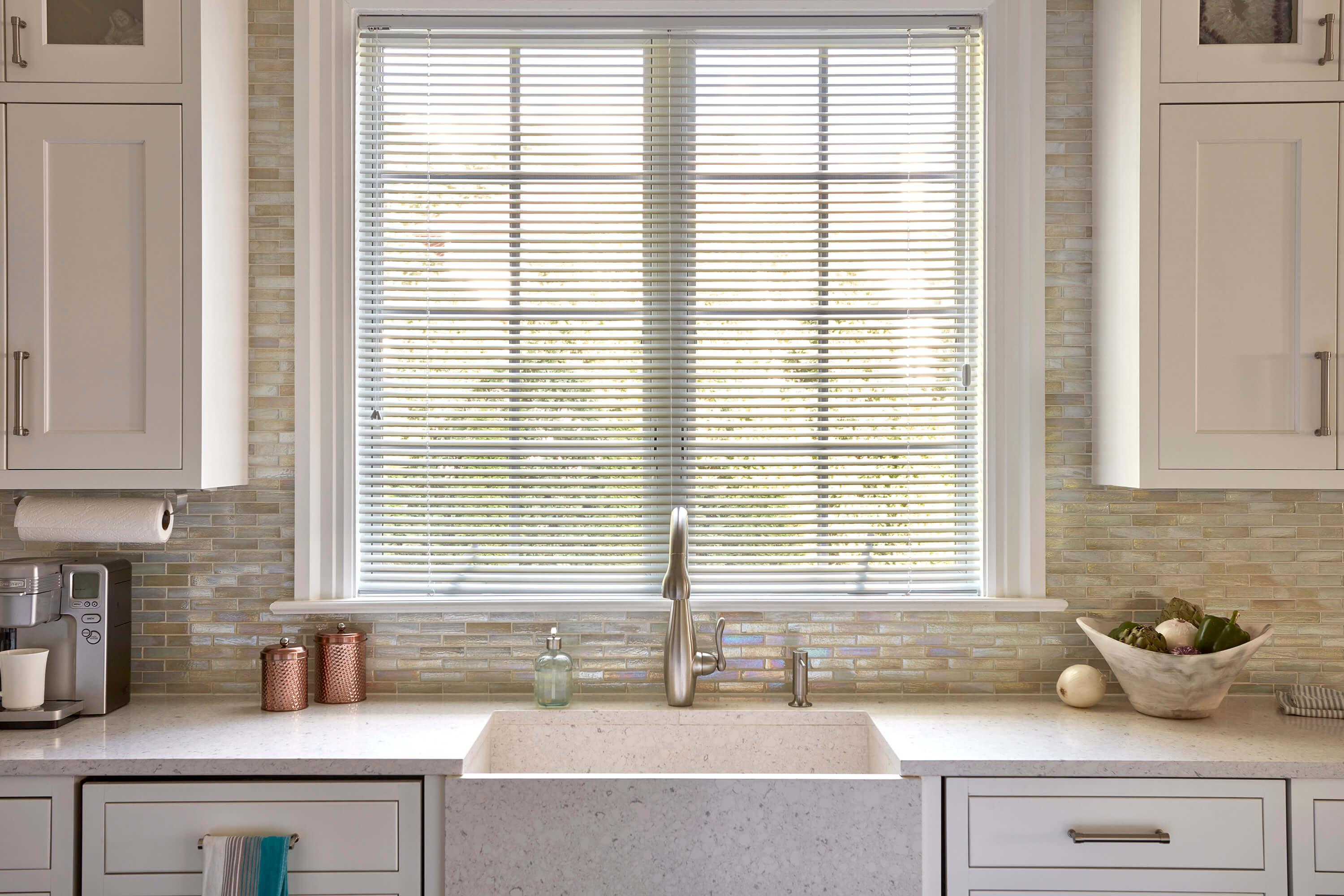 White aluminum mini blinds hang above a large sink in a contemporary kitchen.