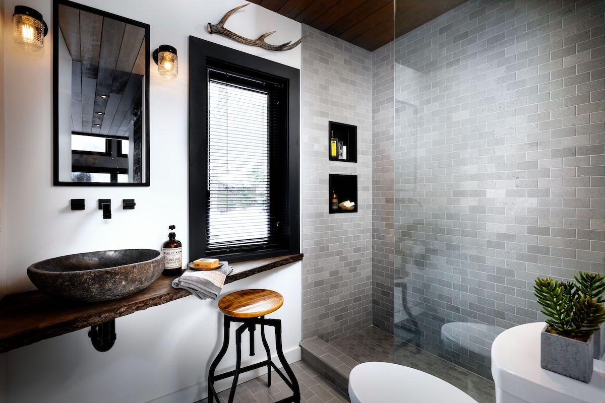 A small modern, rustic bathroom features a window with a black window frame & matte black mini blinds
