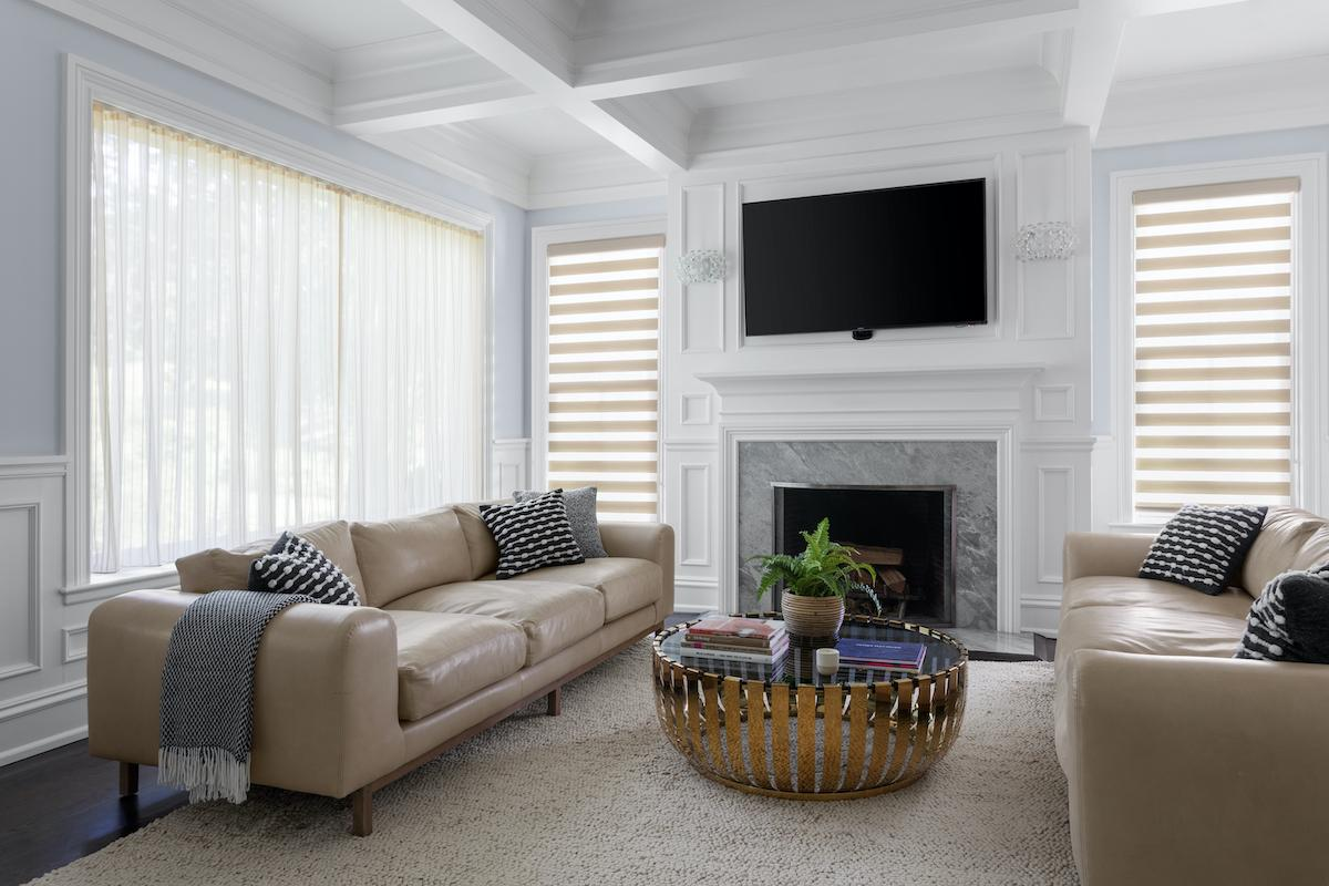 White drapes with a grey chevron print hang in the open position on large windows in a spacious bedroom.
