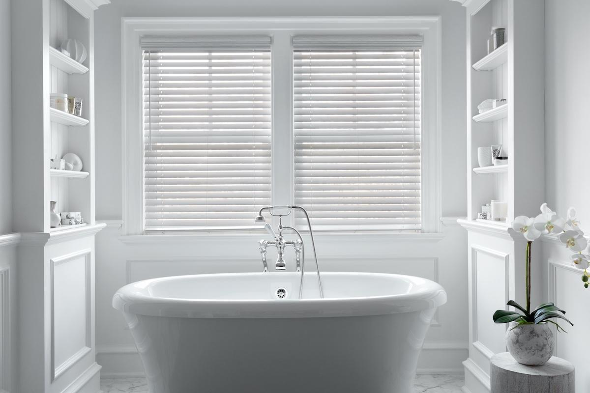 White faux wood blinds cover two windows behind a large modern tub in a contemporary bathroom