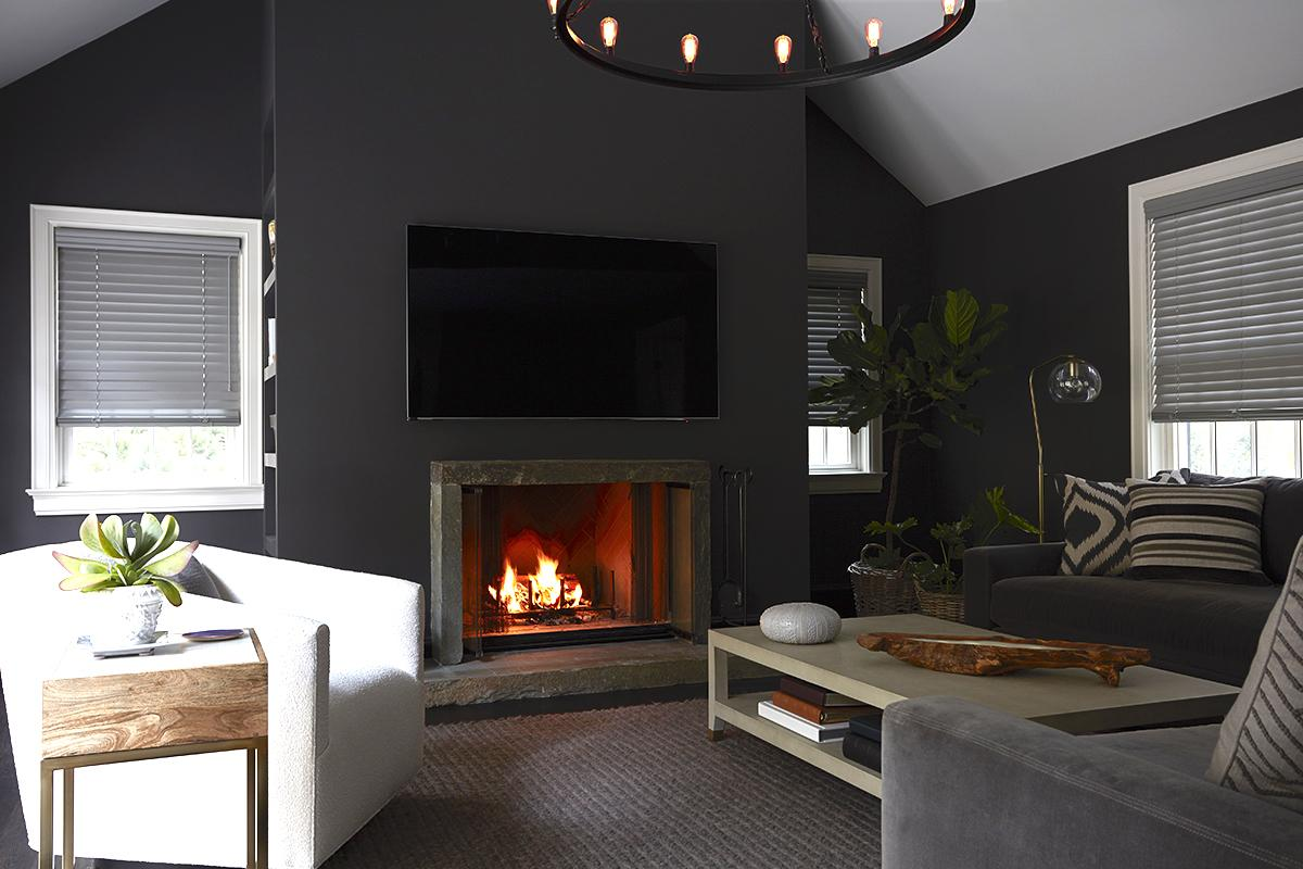 Grey faux wood blinds in a cozy family room with a fireplace and dark grey walls