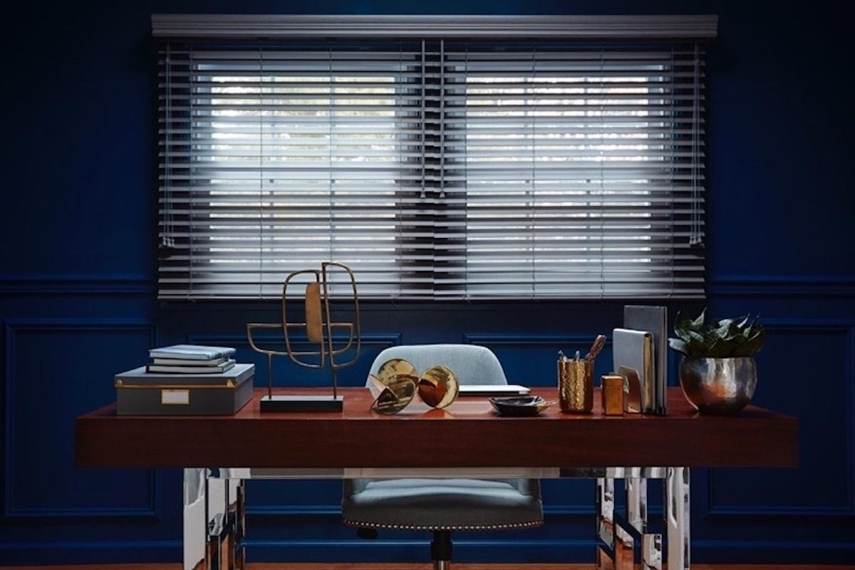 Two dark grey faux wood blinds share one head rail in a contemporary home office