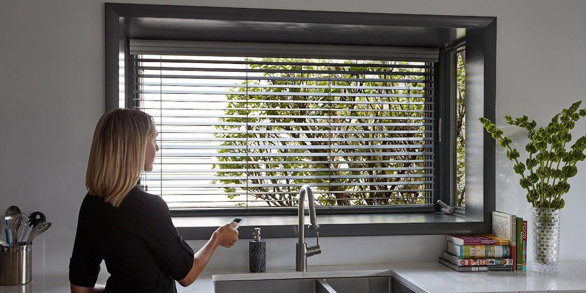 A woman uses a remote to tilt otherwise inaccessible wood blinds in a recessed window over a kitchen sink.