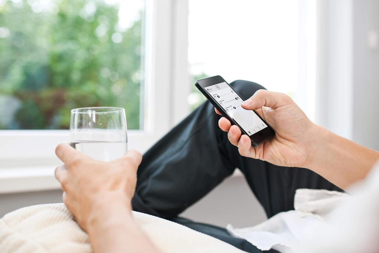 A man relaxes in a comfortable living room chair while using the MOVE app on his mobile phone