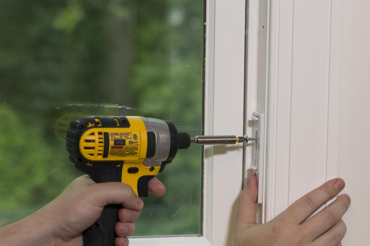 A hand holds the MOVE mounting plate secure on a window frame while mounting it with a drill and a screw