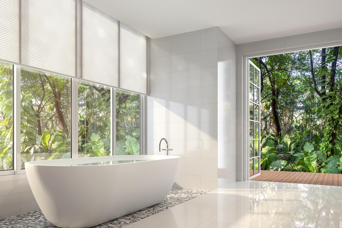 A wall of hard to reach windows behind a large contemporary bathtub show the perfect place for motorized shades.