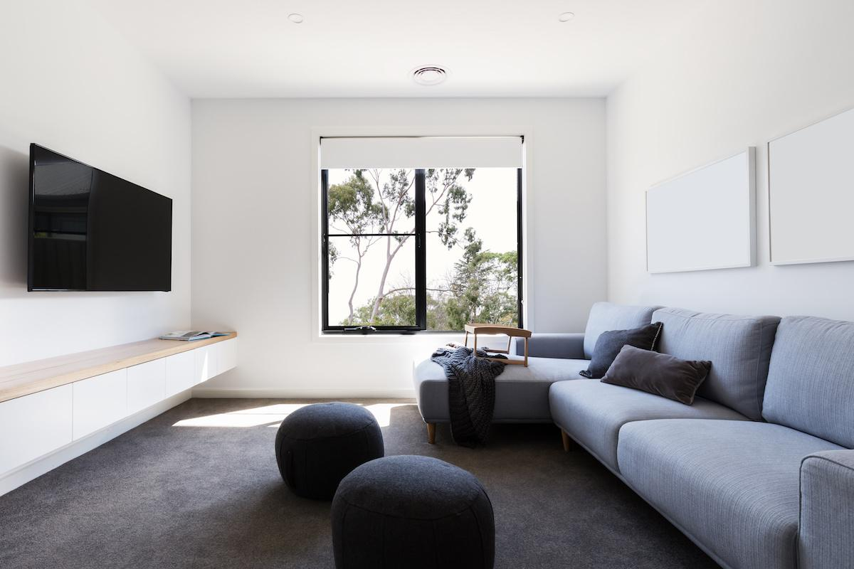 Light pours in through a window in a family room with a cozy couch facing a large television.