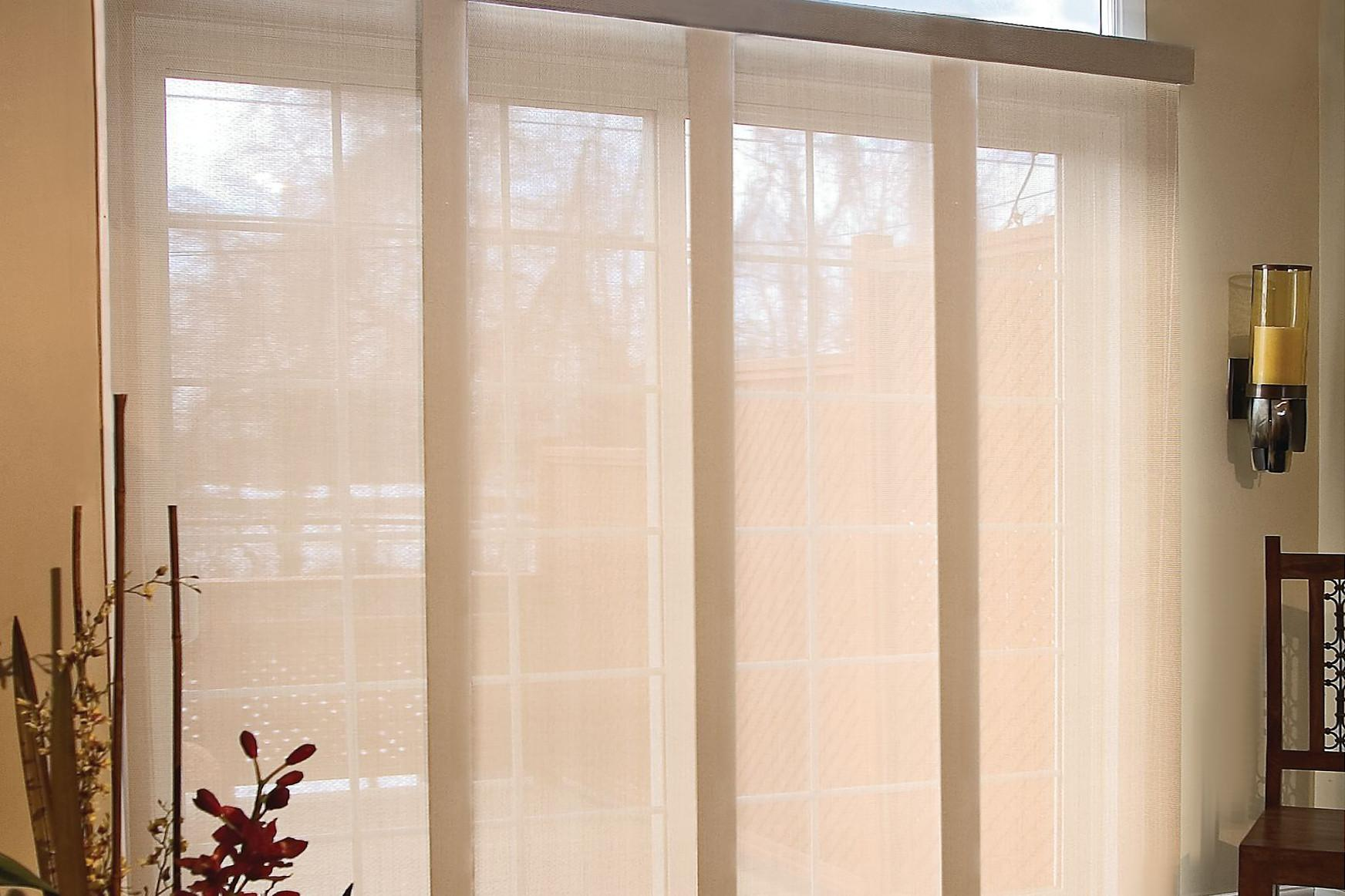 Tan panel tracks blinds constructed of solar shade fabric allow light to filter in while providing privacy in a cozy living room.