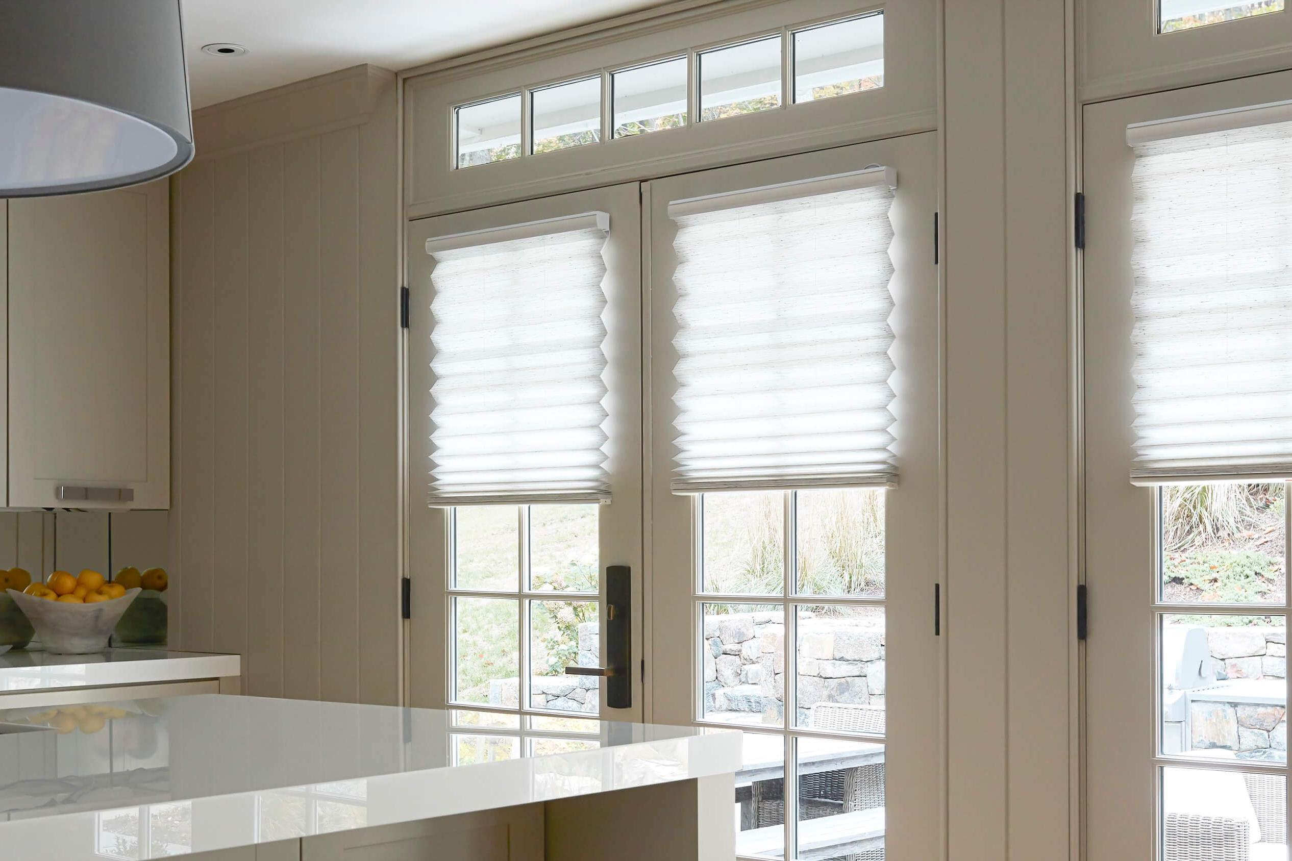 A close up of white pleated shades halfway down on a window