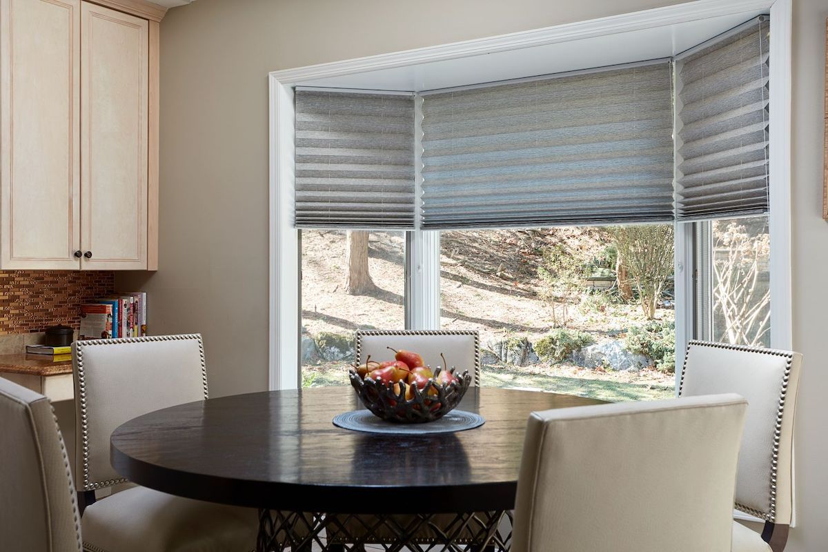 Grey pleated shades partially cover bay windows in a breakfast nook