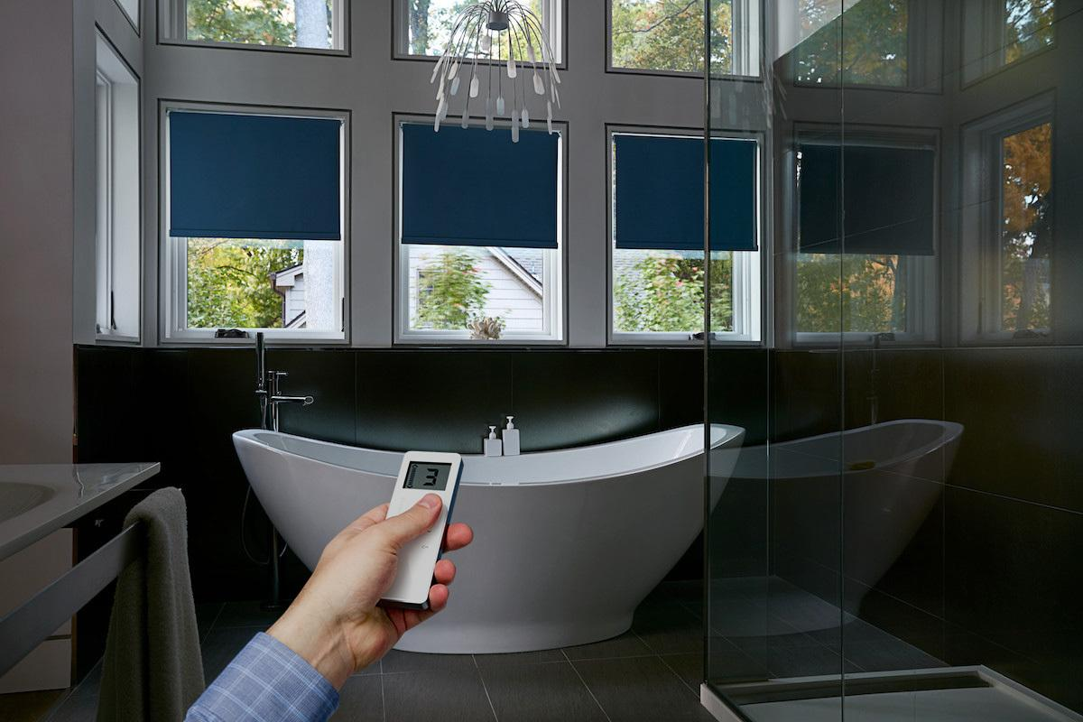 Blue roller shades on three windows behind a large bathtub, with a hand holding a remote in the foreground