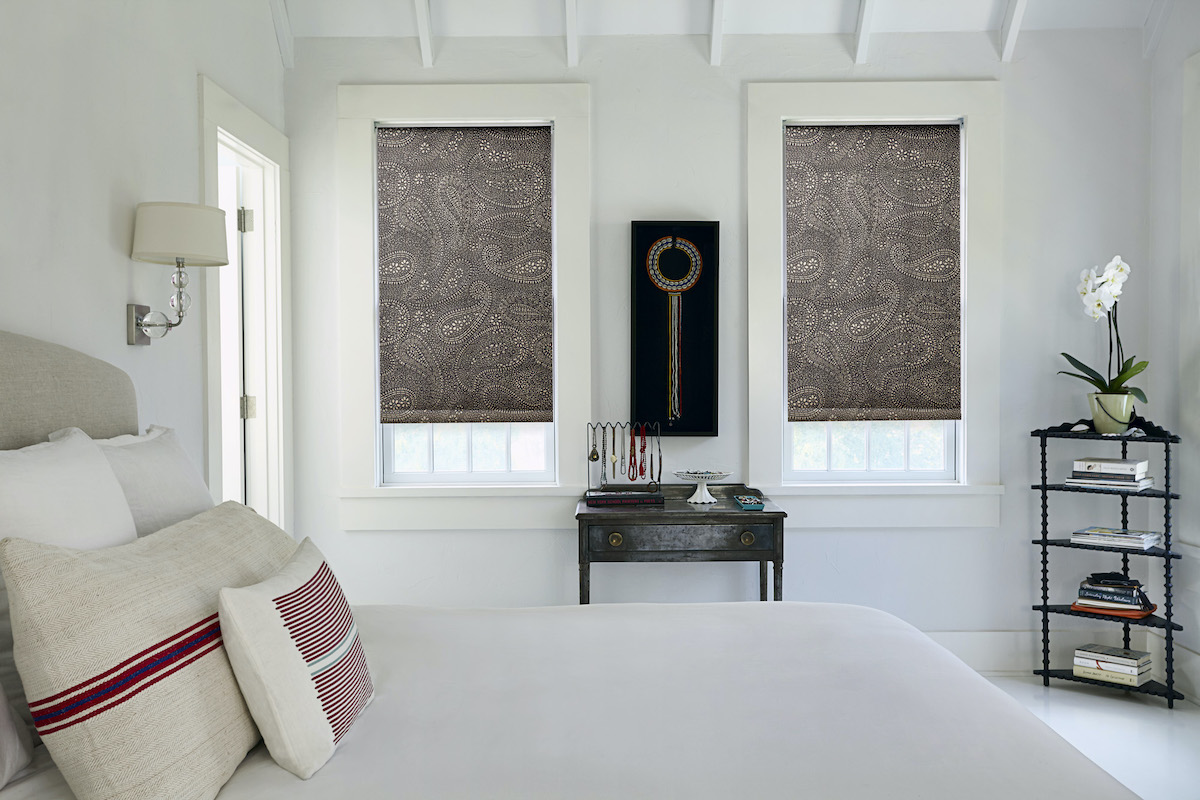 Roller shades in a brown paisley print fabric with no valance in a bright white bedroom