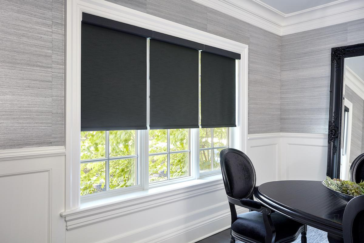 Dark grey roller shades with matching valances in a contemporary white and grey dining room