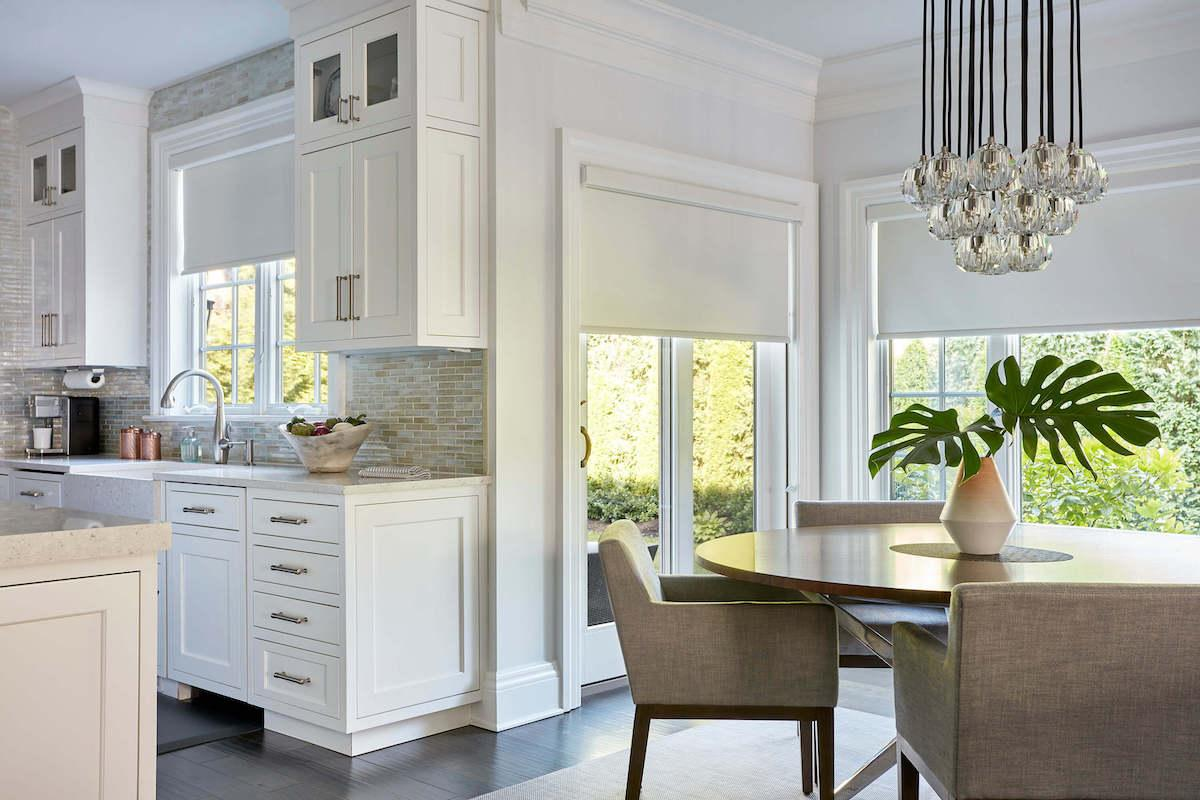 Kitchen and dining room with roller shades in white