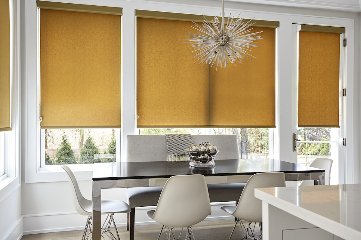 Tan roller shades in a modern dining room
