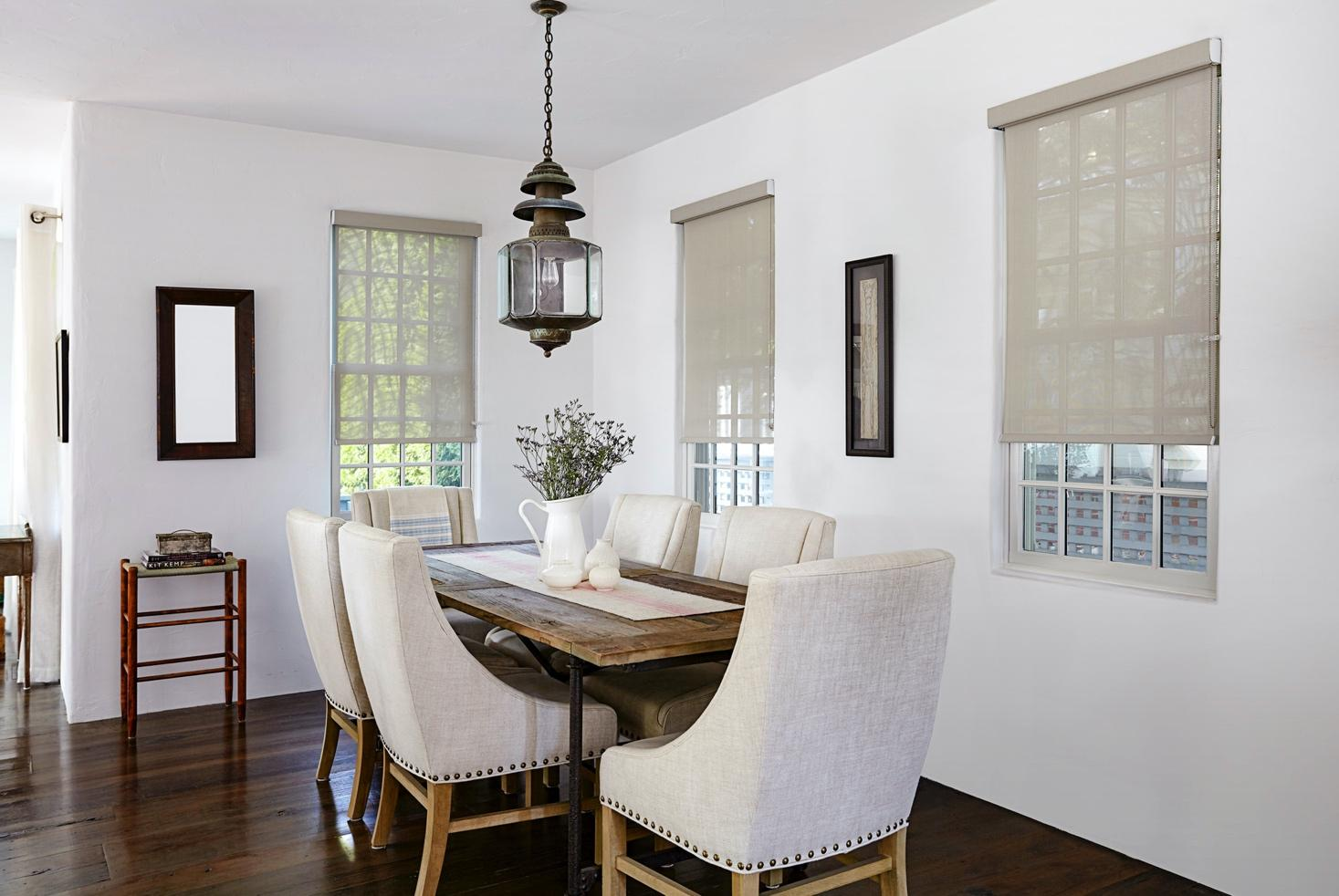 Beige solar shades allow light to filter into a contemporary dining room