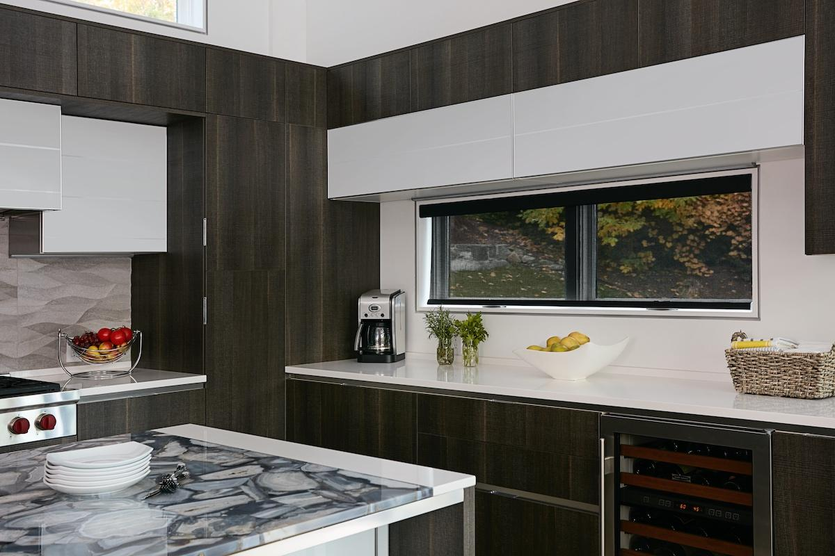 Black solar shades filter out light but allow an unobstructed view in a black and white kitchen