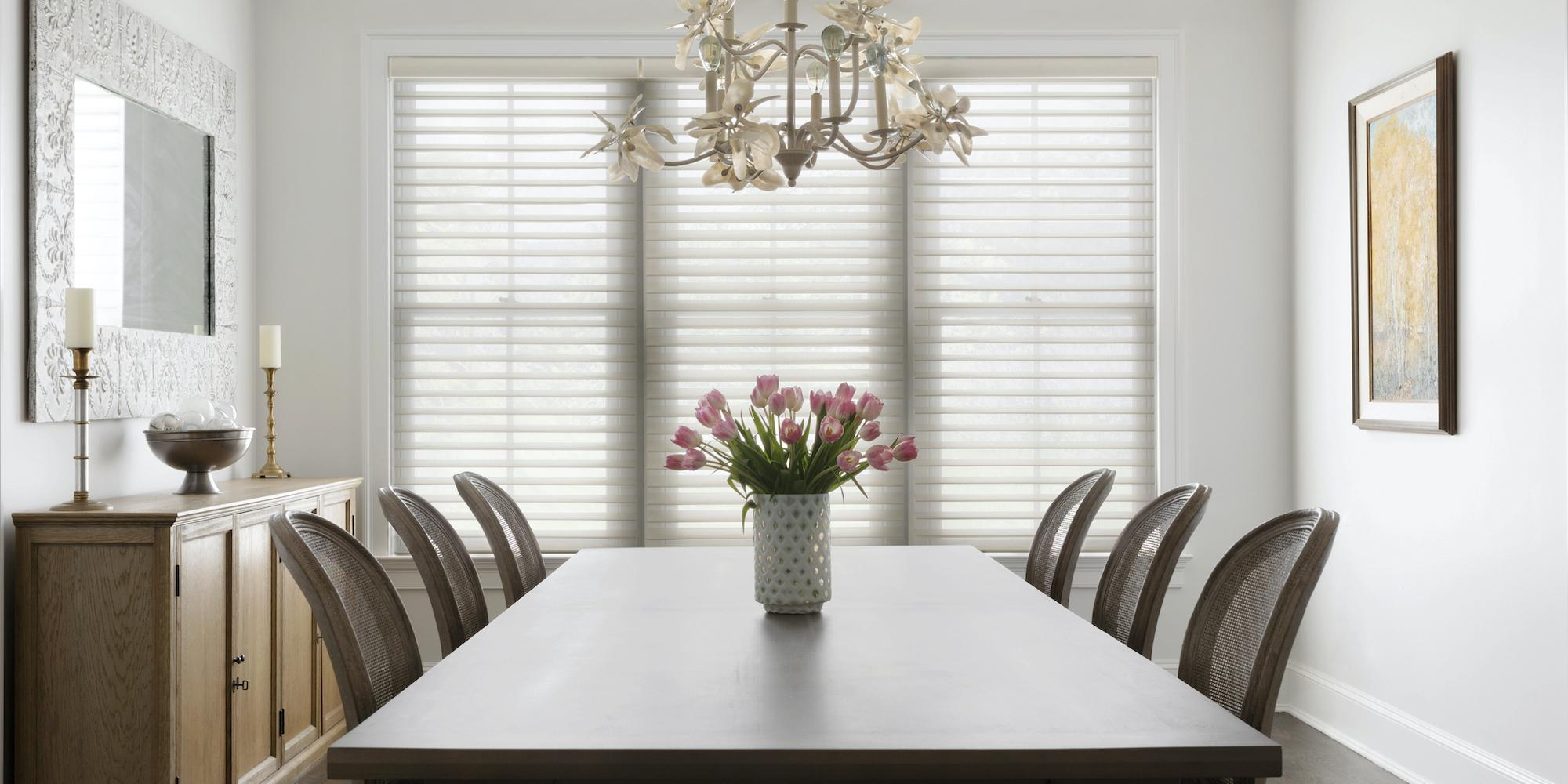 Light pours into a dining room with large windows partially covered with Serenity sheer shades in white