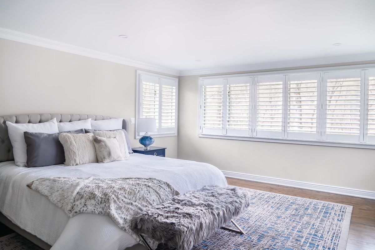 White indoor shutters in a large contemporary bedroom