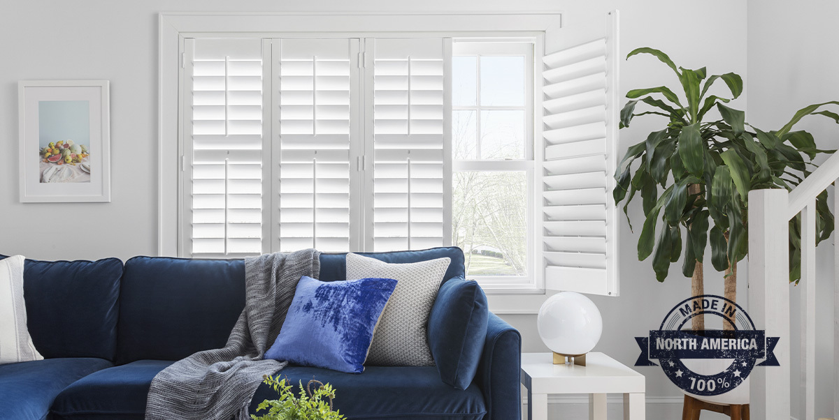 A contemporary living room features indoor shutters on a large window behind a blue velvet couch