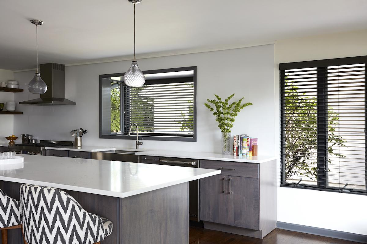 A modern kitchen with white walls and counters features real wood blinds in a dark wood finish on two large windows.