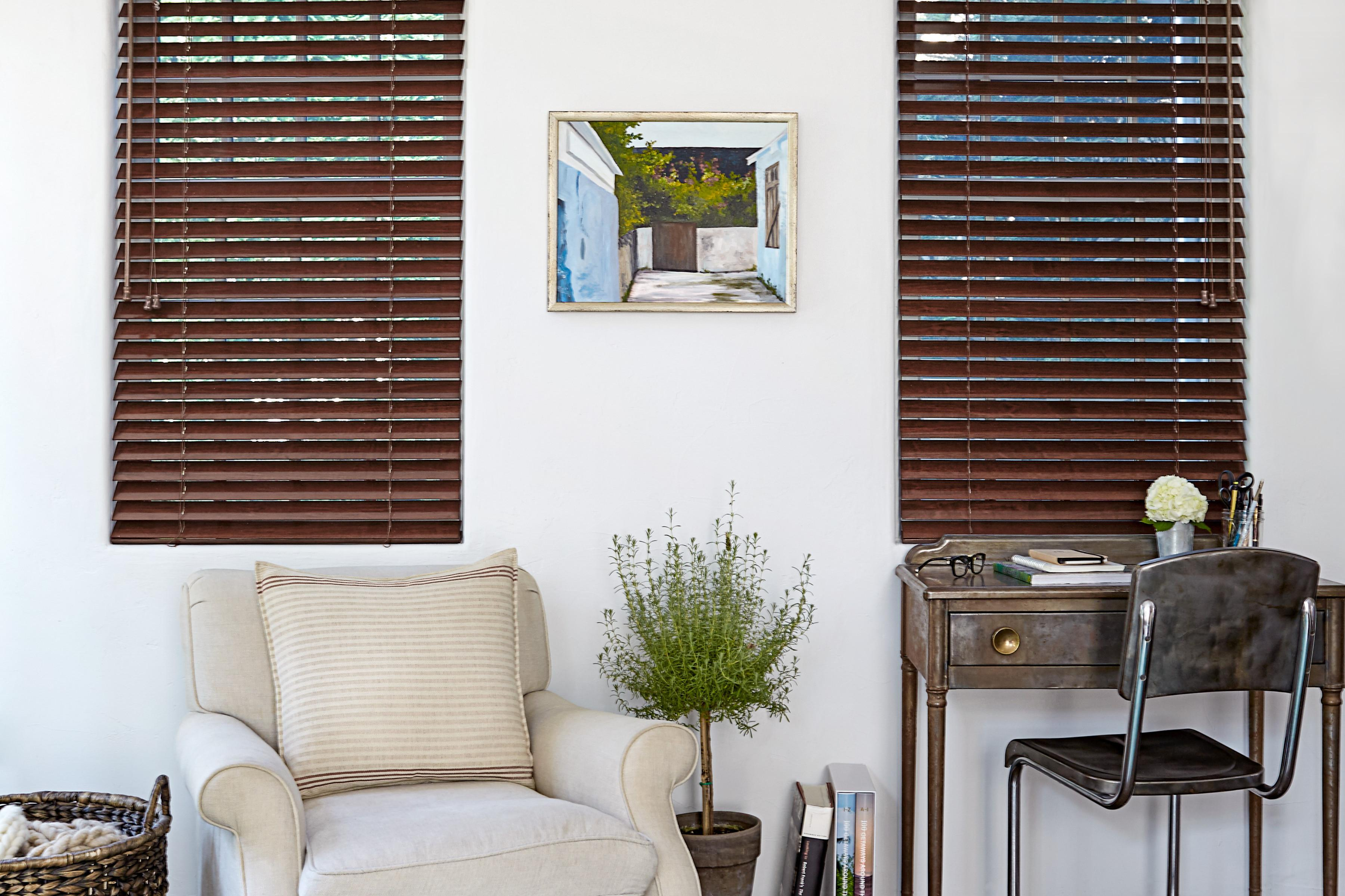 Dark brown real wood blinds cover two windows and lend warmth to a room with white walls, a beige upholstered chair and a small writing desk.