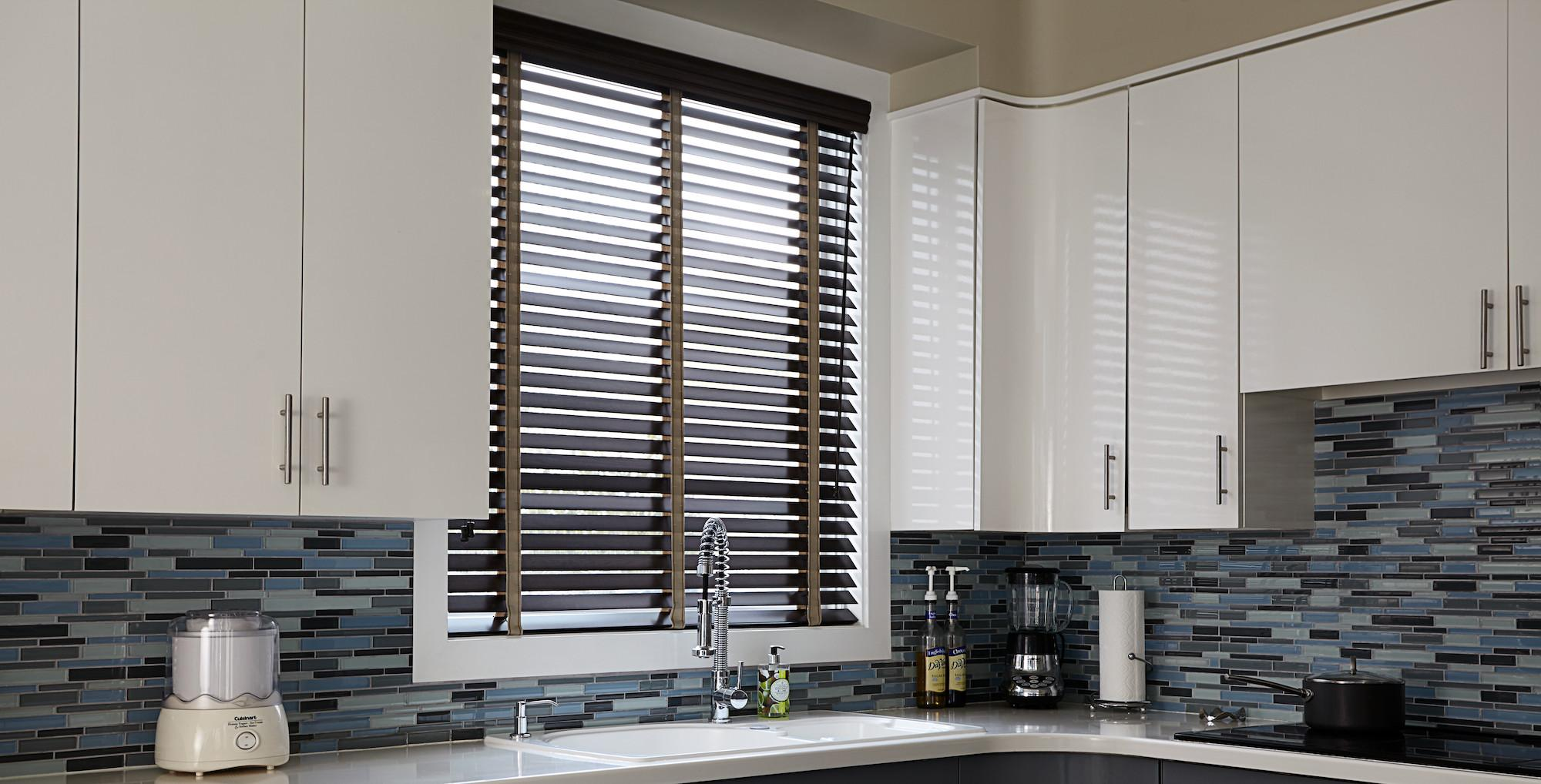 A kitchen window features real wood blinds in a dark brown finish with contrasting tan fabric tape
