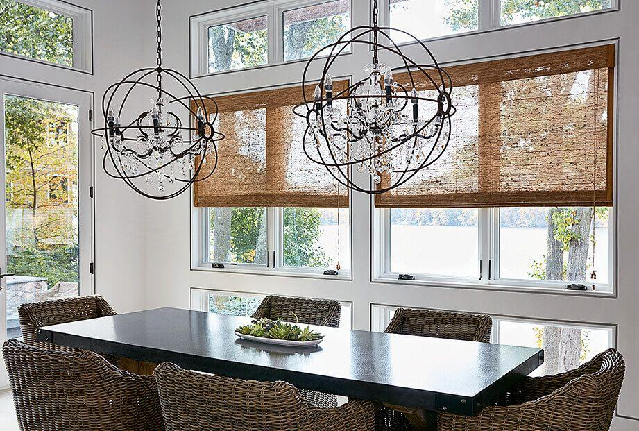 A contemporary dining room showcases woven wood shades on large windows.