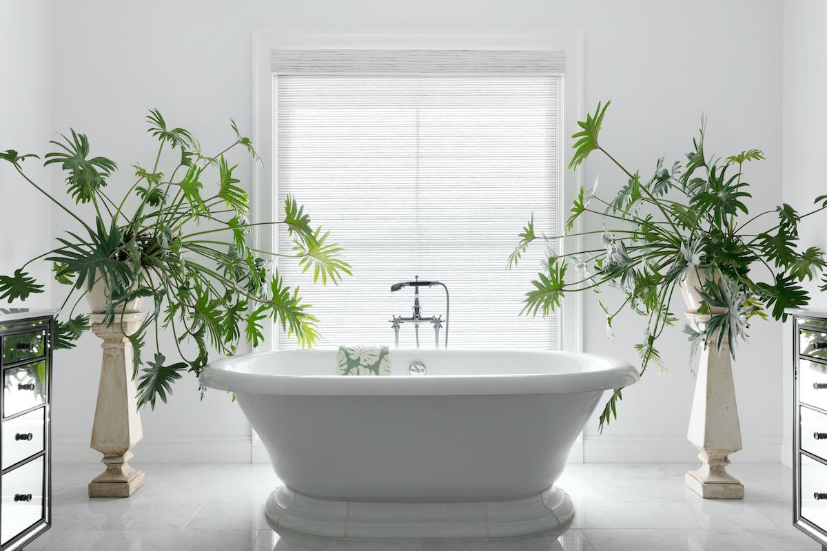 A spacious bathroom features a large freestanding tub flanked by two tropical potted plants with a large window covered in a white-tone woven wood shade in the background