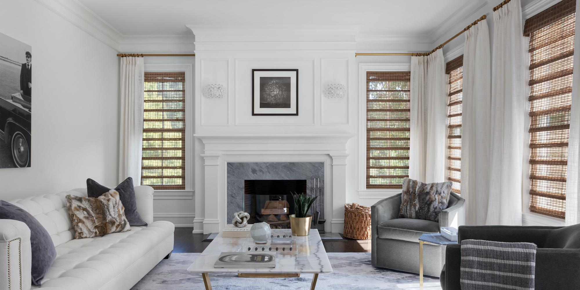A contemporary living room features white linen drapery and unlined woven wood shades in a beautiful natural wood tone