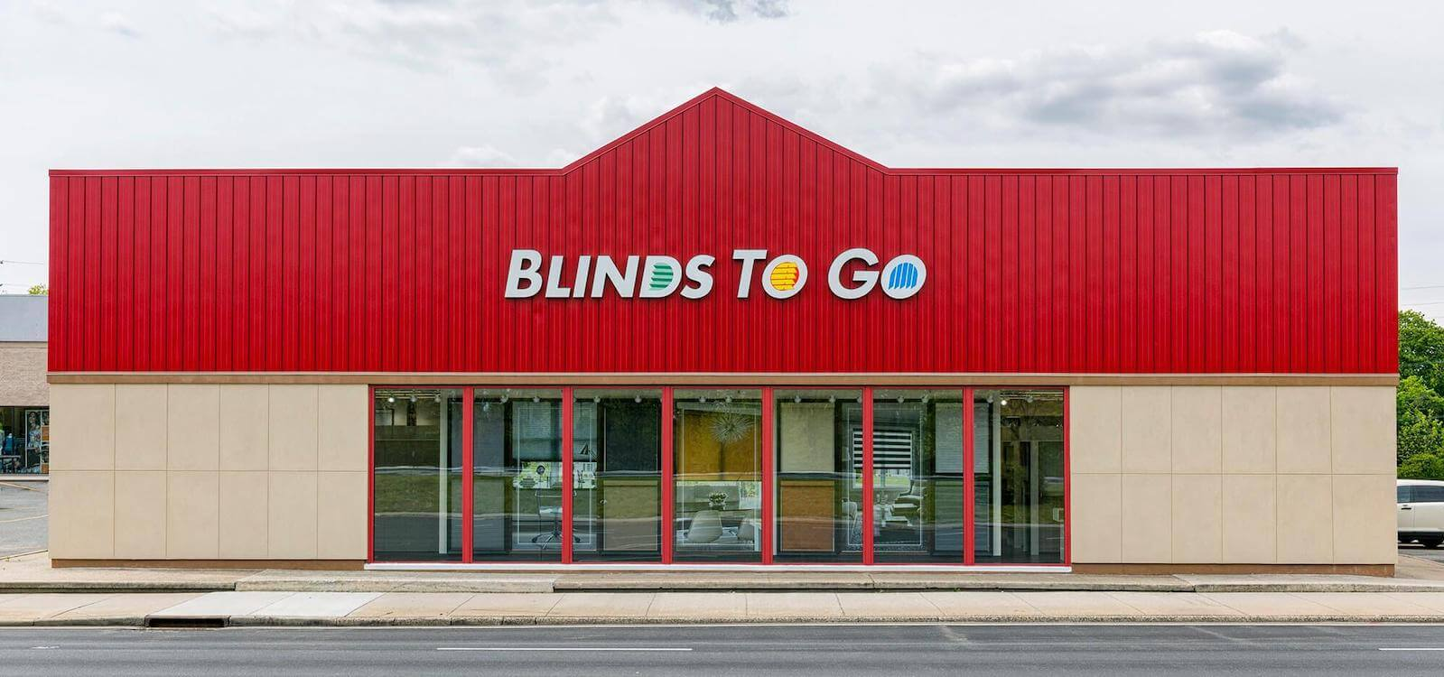 A large Blinds To Go showroom, with its signature red roof, viewed from the parking lot.
