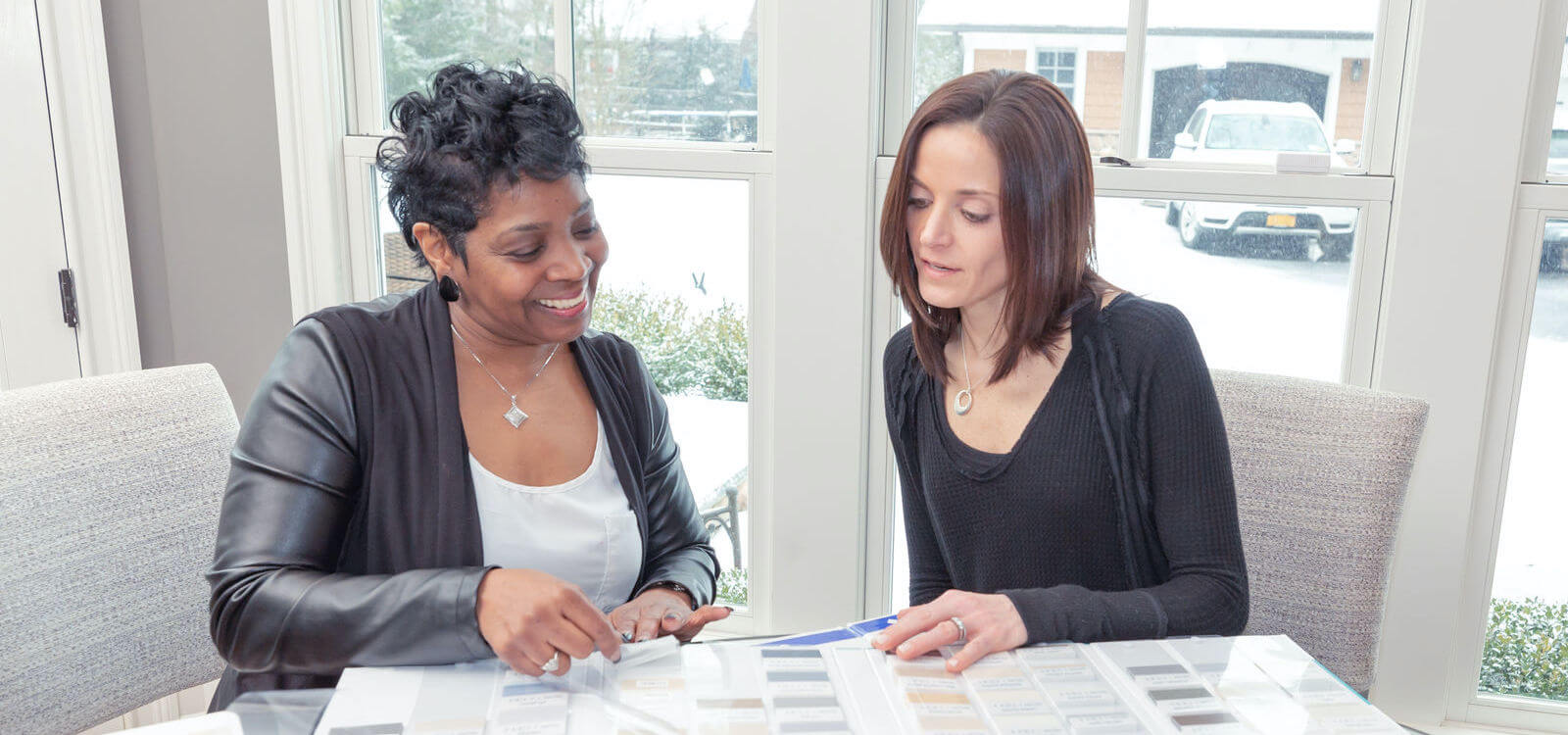 A Shop-at-Home design consultant shows samples to a customer at a dining room table in a modern home.